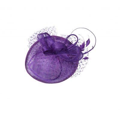 Strohgeflochtene Scheibe mit nach oben gebogener Krempe, gekrönt von wunderschön gelegten Bändern aus selbem Material. Zarte Hahnenfedern und ein umlaufendes filigran geknüpftes Netz unterstreichen den nest-artigen Charakter. Extravagantes Detail: die lange, fein geschliffene Straußenfeder. Auf einem Satin-Haarreifen arrangiert. In Violett.