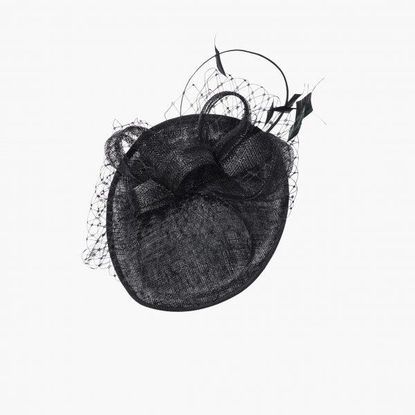 Strohgeflochtene Scheibe mit nach oben gebogener Krempe, gekrönt von wunderschön gelegten Bändern aus selbem Material. Zarte Hahnenfedern und ein umlaufendes filigran geknüpftes Netz unterstreichen den nest-artigen Charakter. Extravagantes Detail: die lange, fein geschliffene Straußenfeder. Auf einem Satin-Haarreifen arrangiert. In Schwarz.